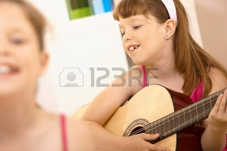 8783916-young-girl-enjoying-playing-guitar-smiling-at-home