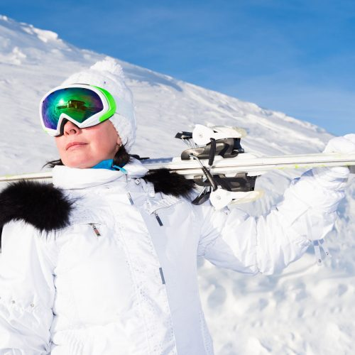 52447078 - woman skier in a white suit mountain top in snow