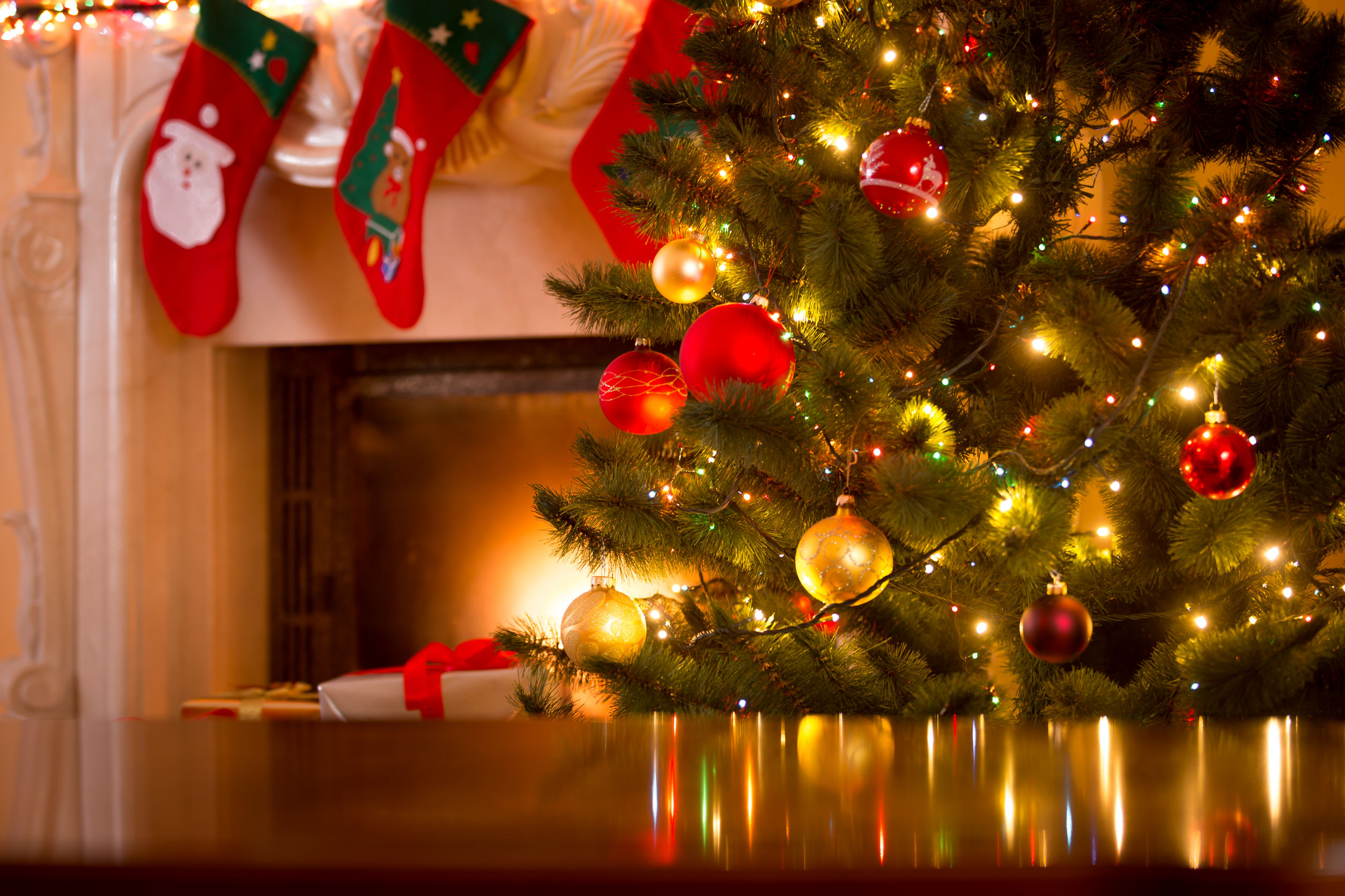 45224312 - christmas holiday background of wooden table against decorated christmas tree and fireplace